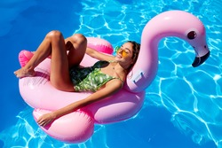 Young smiling fitted girl in bikini relax chilling on pink inflatable flamingo in swimming pool. Attractive woman in swimsuit lies in a sun on tropical vacation. Pretty female sunbathing at resort.