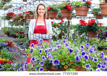 Young smiling florist working in the greenhouse.