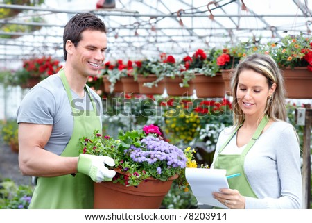 Young smiling florists working in the greenhouse.