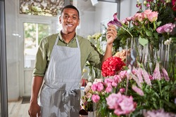 Young smiling flower shop manager standing near the entrance and looking at camera while keeping his hand on a flower