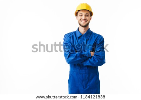 Young smiling foreman in blue uniform and yellow helmet happily looking in camera with cross hands over white background