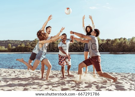 young smiling friends playing beach volleyball on riverside at daytime