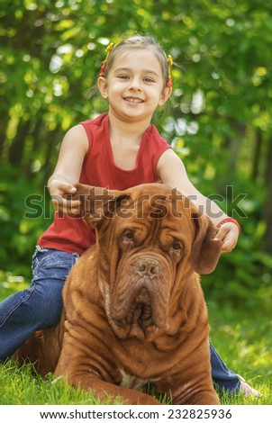 Young smiling girl astride big dog of breed FRENCH MASTIFF, DOGUE DE BORDEAUX