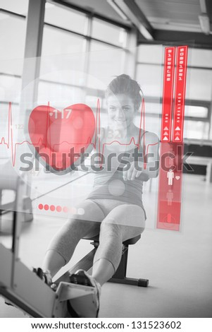 Young smiling girl doing rowing machine with futuristic interface in black and white