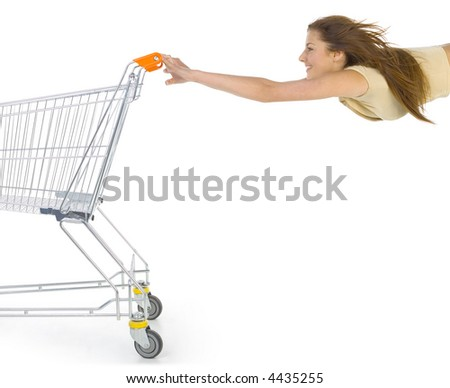 Young smiling girl holding full of things trolley. Flying with trolley. Side view