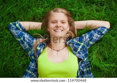 Young smiling girl in green vest relaxing in soft grass