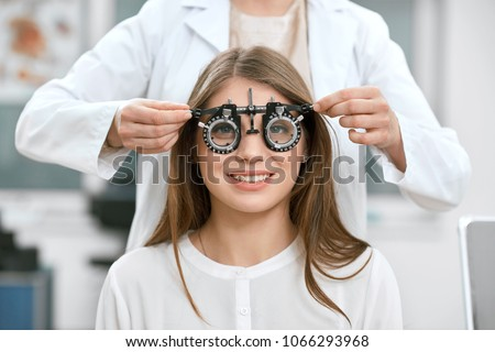 Young smiling girl is sitting and looking at camera through during vision checking. Ophthalmologist is using special medical equipment for eye health saving and improving.