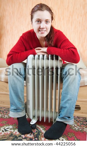 young smiling girl is sitting by a oil heater