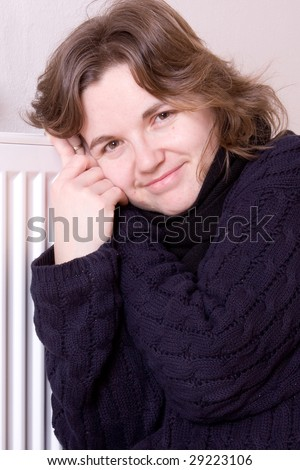 young smiling girl is sitting by a white heater