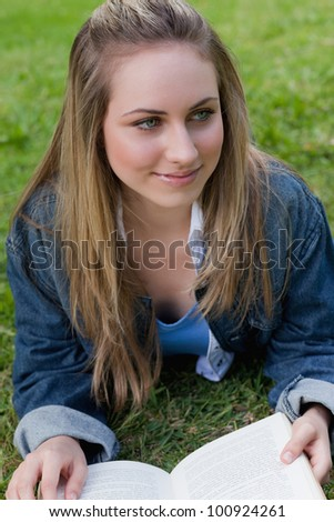 Young smiling girl looking away while lying on the grass in a park and reading