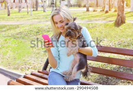 Young smiling girl owner with yorkshire terrier dog sitting in the park
