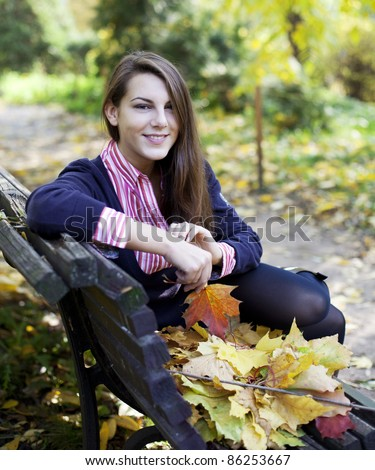 Young smiling girl sitting on bench in park holding fallen leaves