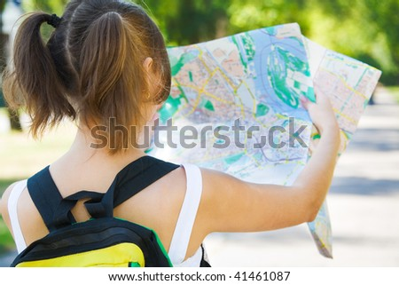 Young smiling girl with backpack holding city map