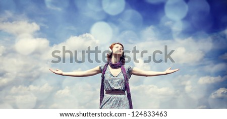 Young  smiling girl with headphones at blue sky background