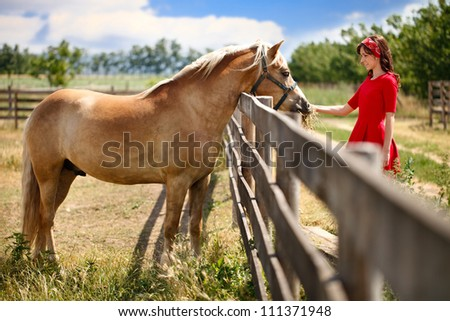 Young smiling girl with her horse
