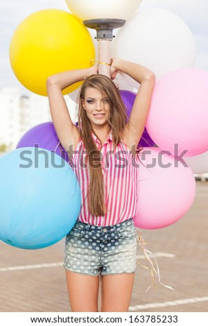 young smiling girl with messy hair in short denim shorts and sleeveless striped top leans on light-pole holding bunch of bright balloons