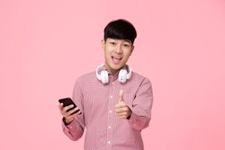 Young smiling handsome Asian man with headphones and smartphone giving thumbs up studio shot isolated on white background