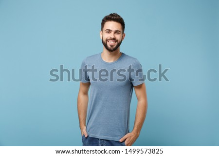 Young smiling handsome man in casual clothes posing isolated on blue wall background, studio portrait. People sincere emotions lifestyle concept. Mock up copy space. Holding hands in pockets Foto d'archivio ©