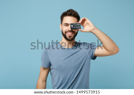 Young smiling handsome man in casual clothes posing isolated on blue wall background studio portrait. People sincere emotions lifestyle concept. Mock up copy space. Covering eye with credit bank card