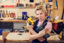 Young smiling handy woman with short blond hair working with screwdriver.