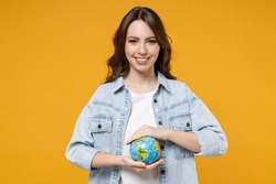 Young smiling happy brunette fun geography student woman 20s wearing stylish casual denim shirt white t-shirt holding in palms Earth world globe isolated on yellow color background studio portrait.