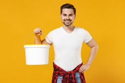 Young smiling happy employee handyman man wear t-shirt holding paint bucket isolated on yellow background studio portrait. Instruments accessories for renovation apartment room. Repair home concept