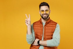Young smiling happy friendly cheerful fun caucasian man 20s wear orange vest mint sweatshirt glasses show victory v-sign gesture isolated on yellow background studio portrait. People lifestyle concept