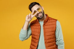 Young smiling happy friendly cheerful fun man 20s in orange vest mint sweatshirt glasses cover eyes with victory v-sign gesture isolated on yellow background studio portrait. People lifestyle concept