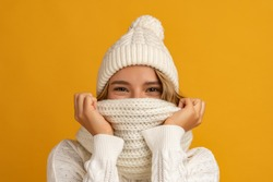 young smiling happy pretty blond woman wearing white knitted sweater, scarf and hat, warm winter cold season fashion accessories trend, posing on yellow studio background isolated