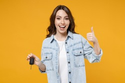 Young smiling happy satisfied excited successful lucky brunette woman 20s in denim shirt white t-shirt hold in hands car keys show thumb up like gesture isolated on yellow background studio portrait