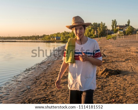 young smiling happy teenage boy in summer hat with towel on the sea coast beach during golden hour #1114181552