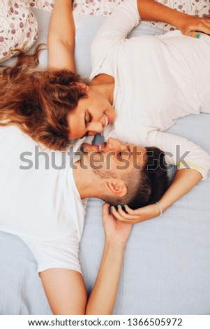 Young smiling heterosexual couple lying down together on the bed #1366505972