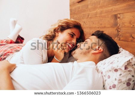 Young smiling heterosexual couple lying down together on the bed #1366506023