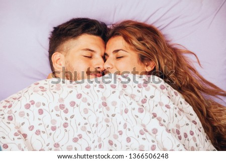 Young smiling heterosexual couple lying down together on the bed #1366506248