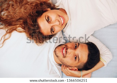 Young smiling heterosexual couple lying down together on the bed #1366506251