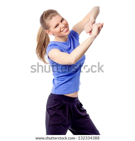 Young smiling instructor doing aerobics dance, isolated on white background. Happy active Caucasian woman enjoying fitness