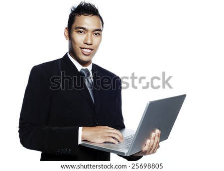 Young smiling malay entrepreneur businessman wearing business suit and giving a presentation with his laptop computer.