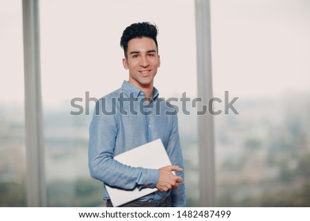 Young smiling male at window with laptop portrait #1482487499