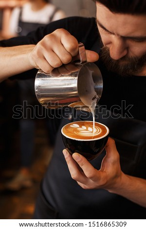 Young smiling male barista making cappuccino. Pouring milk for prepare cup of coffee. Latte art. Morning cup of coffee in café. Brewing coffee. Coffee shop concept.