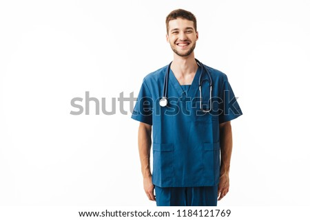 Young smiling male doctor in uniform with phonendoscope on neck joyfully looking in camera over white background