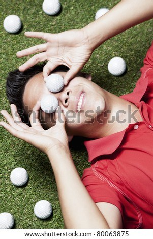 Young smiling male golf player in red shirt lying on green next to several golf balls and covering his eyes with two golf balls.