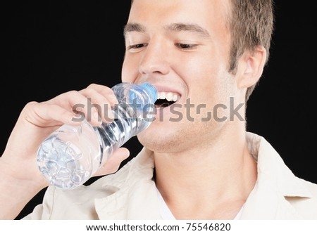 Young smiling man drinks water from bottle, on black background.
