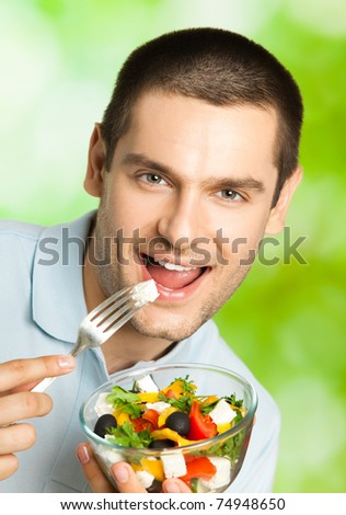 Young smiling man eating salad, outdoors