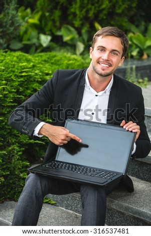 Young smiling man is sitting on the stairs. He is pointing his finger to the laptop. He is happy a lot