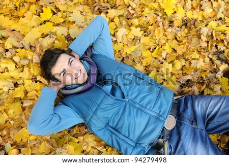 Young smiling man portrait laying in foliage in autumn park. Outdoor.