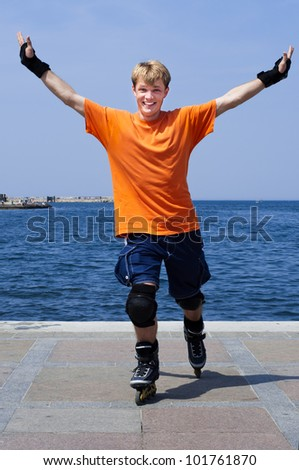 Young smiling man rollerskating with the sea in background