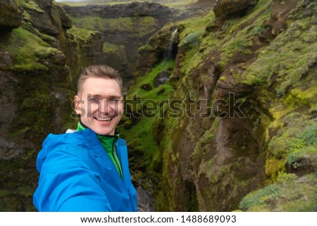 Young smiling man with river and green canyon on background takes a Selfie. Concept of freedom movement and freedom