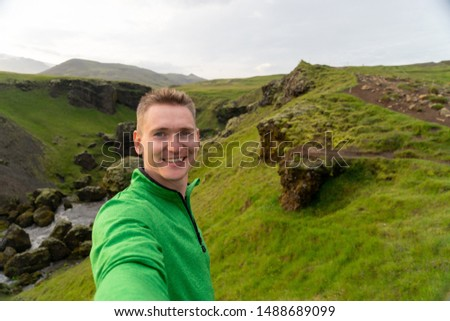 Young smiling man with river and green mountains on background takes a Selfie. Concept of freedom movement and freedom