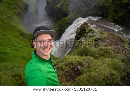 Young smiling man with waterfall and green canyon on background takes a Selfie. Concept of freedom movement and freedom