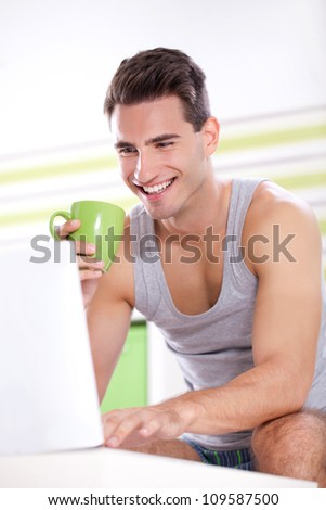 Young smiling men drinking coffee and using laptop in morning